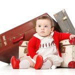 Baby in red with suitcases